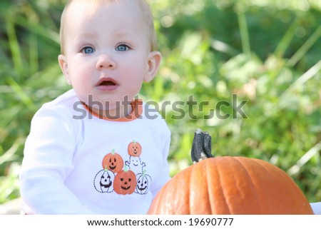 Adorable blue eyed baby boy with a pumkin, suitable for a variety of seasonal themes - stock photo