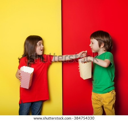 Adorable boy and girl having great time eating popcorn, on red and yellow background - stock photo