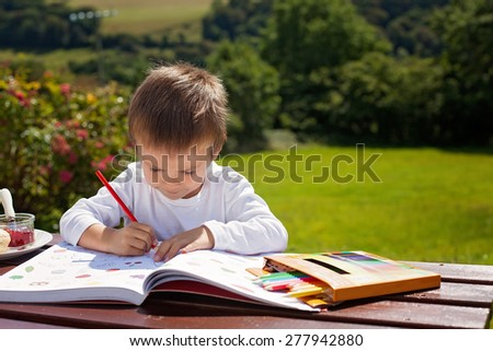 Adorable boy, drawing a painting in a book, outdoor in the garden, sitting on a bench - stock photo