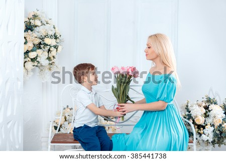adorable boy gives her mother a bouquet of flowers on March 8 Happy Birthday - stock photo