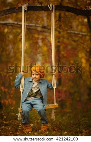 Adorable boy having fun on a swing on beautiful autumn day. Elegant boy swinging on a swing, like a man. Chestnut autumn childhood sunset. - stock photo