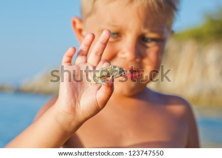Adorable boy holding crab on hand on the beach. Focus on the crab. - stock photo