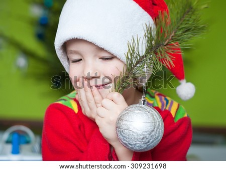 Adorable boy in a Christmas costume and Christmas toy in his hands - stock photo