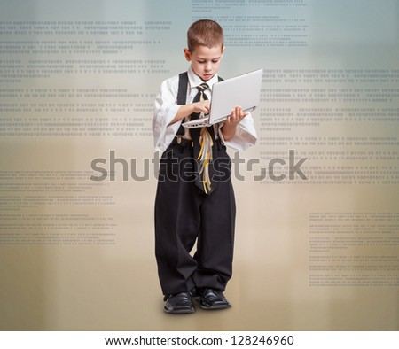 Adorable boy in father's business suit with laptop