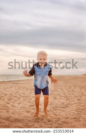 adorable boy jumping on the beach - stock photo