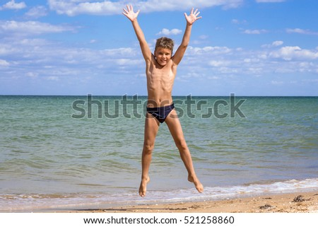 Adorable boy jumping on the beach against blue sky