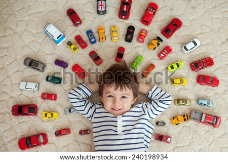 Adorable boy, lying on the ground, toy cars around him , looking at the camera, shot from above - stock photo