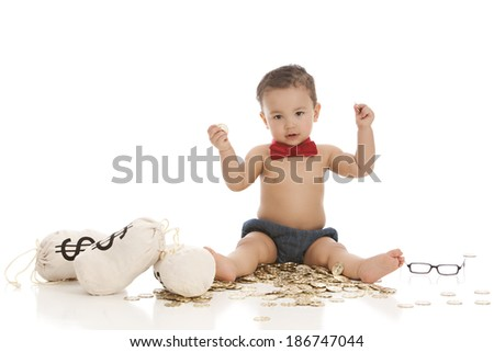 Adorable boy sitting on a pile of gold coins with money bags.  Isolated on white. - stock photo