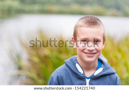 Adorable boy with retainer on teeth smiling outdoors - stock photo