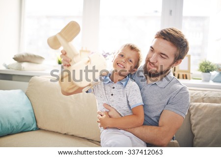Adorable boy with wooden airplane playing with his father