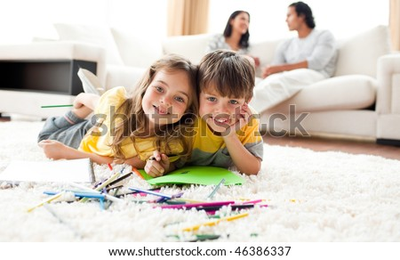 Adorable brother and sister drawing lying on the floor in the living room - stock photo