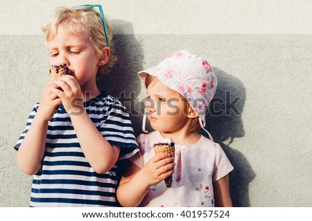 Adorable brother and sister eating ice cream - stock photo
