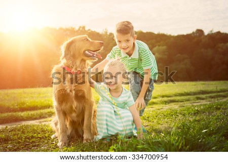 Adorable brother and sister playing with pet dog - stock photo