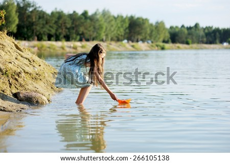 Adorable brunette kid girl playing with paper boat at the lake in the evening sunlight - stock photo