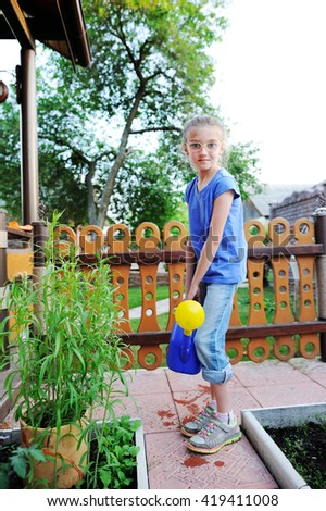Adorable brunette kid girl, watering the plants, from hose spray in the garden at the backyard of the house on a sunny summer evening - stock photo
