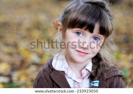 Adorable brunette kid girl with big blue eyes in the fall forest - stock photo