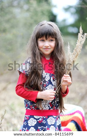 Adorable brunette little girl with very long hair in colorful dress poses outdoors