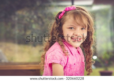 Adorable brunette young girl in pink clothing looking to camera with nice smile, garden background.