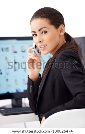 Adorable business woman talking cell phone while sitting in front of computer monitor - stock photo