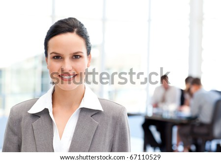 Adorable businesswoman standing in front of her team while working in the background