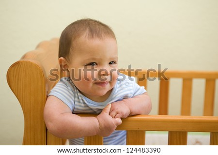 Adorable Caucasian baby boy smiling in his crib in the nursery