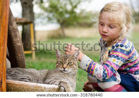 adorable caucasian blond girl caressing domestic cat