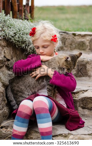 adorable caucasian blond girl sitting in stairs and caressing domestic cat  - stock photo
