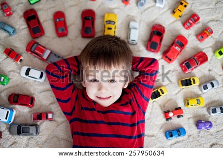 Adorable caucasian little boy in red and blue striped shirt, lying on the ground, red, yellow, blue and white toy cars around him , looking and smiling at the camera, shot from above - stock photo