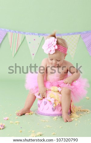 Adorable cheeky blond haired baby girl in tutu with flower in hair sitting on vanilla sponge cake touching icing with pink and purple hearts with green seamless background and flag bunting behind her