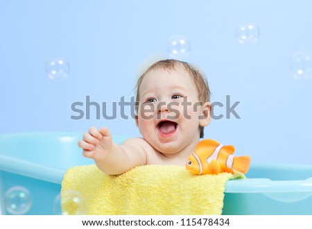 adorable child boy taking bath in blue tub - stock photo