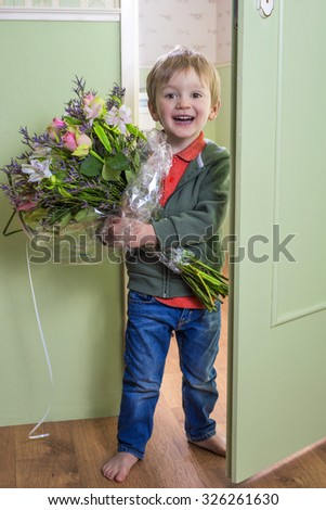 Adorable child bringing a bouquet of flowers - stock photo