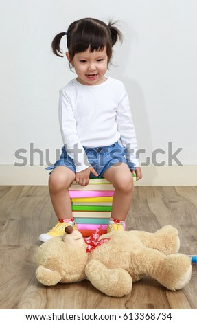 Adorable child doctor examining plush toy over white
