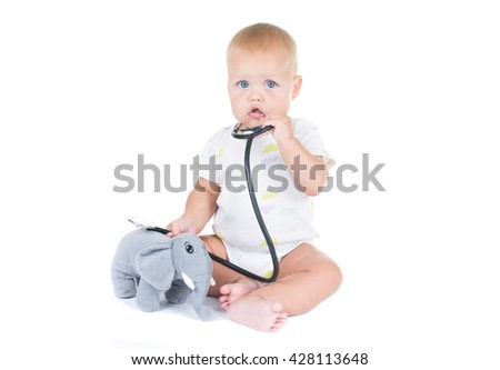 Adorable child dressed as doctor playing with toy oIsolated on white background