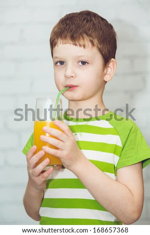 Adorable child drinking orange juice out of the tube, closeup horizontal image on a light background.