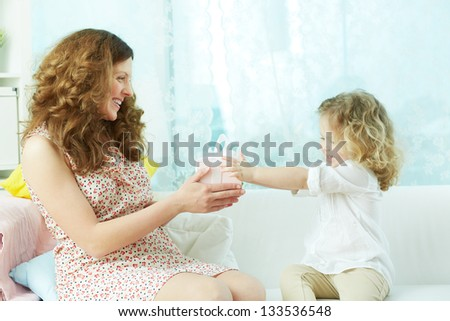 Adorable child expressing her love by giving a present to her mom - stock photo