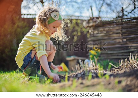 adorable child girl in sunny spring garden planting flowers  - stock photo
