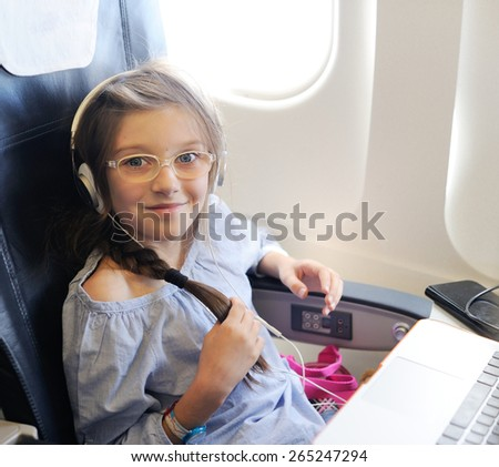 Adorable  child girl with headphones and laptop in the plane - stock photo