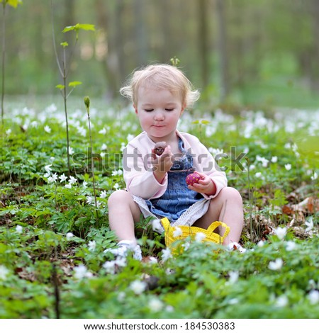 Adorable child, happy blonde toddler girl, playing in the forest full of beautiful white flowers eating chocolate and hunting for eggs on a sunny Easter day