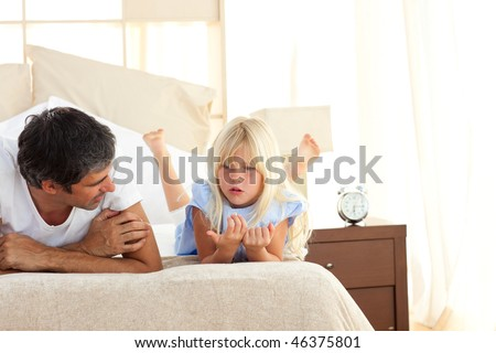Adorable child having discussion with her father lying on bed - stock photo
