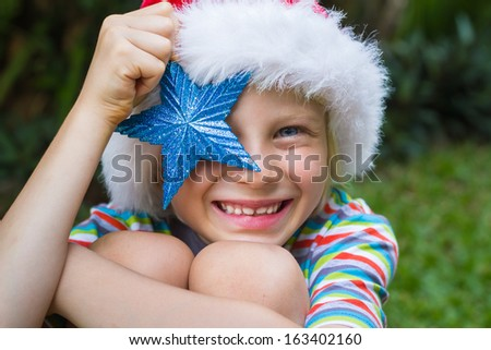 Adorable child holding a glittering blue star and wearing a Santa hat - stock photo