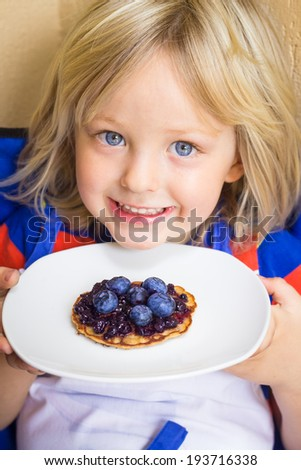 Adorable child holding a healthy homemade wholemeal pikelet with fresh blueberries and jam on top - stock photo