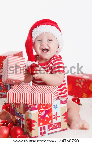 Adorable child is sitting on floor, wearing red Christmas cap, ired balls and presents around. isolated on white background - stock photo