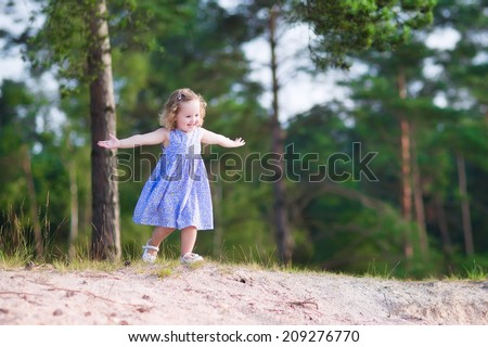 Adorable child, little curly toddler girl in a blue summer dress running and playing on sand dunes in a beautiful pine wood forest enjoying hiking on a warm sunny day - stock photo