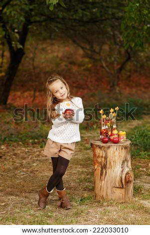 Adorable child playing in autumn park with sweet autumn decoration. - stock photo