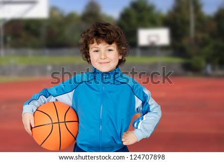Adorable child playing the basketball in the basket field - stock photo
