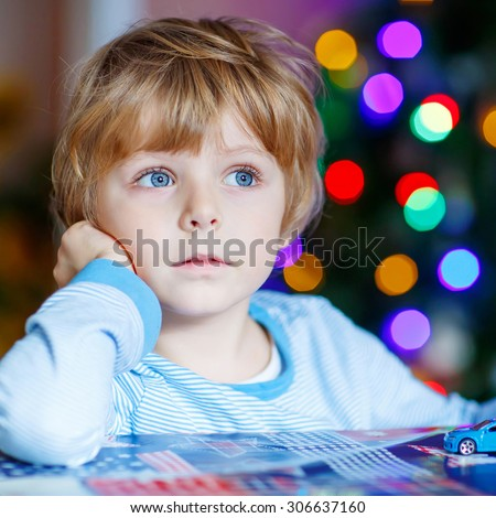 Adorable child playing with cars and toys at home, indoor. funny boy having fun with gifts. Colorful christmas lights on background. Family, holiday, kids lifestyle concept. - stock photo