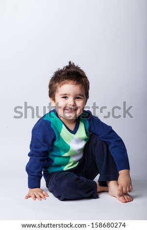 Adorable child sitting on the floor isolated on white background - stock photo