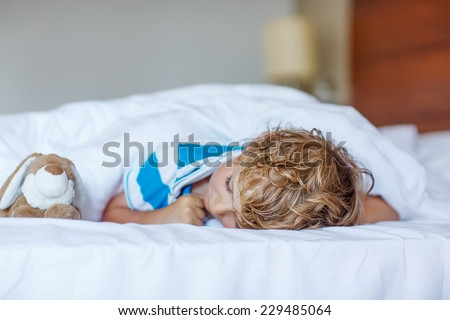 Adorable child sleeping and dreaming in his white bed with toy. - stock photo