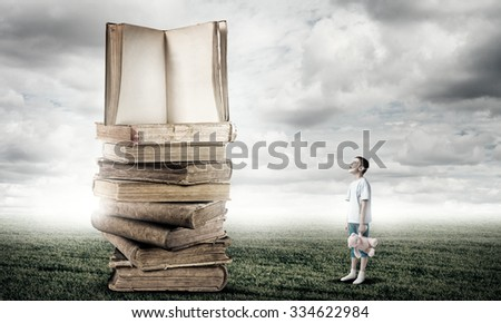Adorable child standing with bear toy in hand and pile of old books - stock photo
