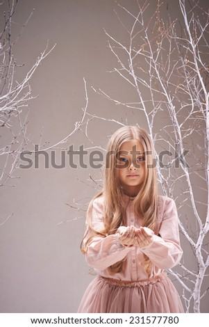 Adorable child with heap of snowflakes on her palms looking at camera - stock photo